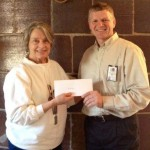 Club member Marilee Shortreed presents Museum Supervisor Pat McKay with a donation for Van Hoosen Farm.