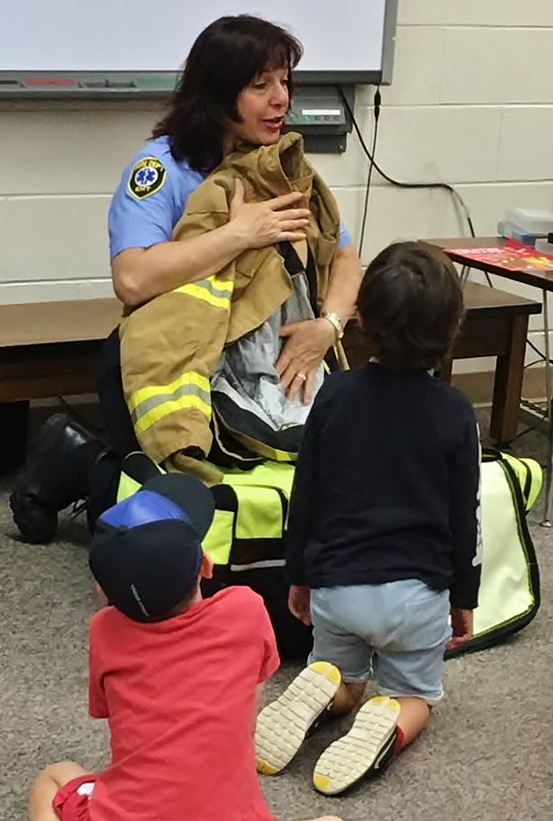 Nancy Butty, Public Education Specialist from the Rochester Hills Fire Department, shows Safety Town attendees a firefighter uniform