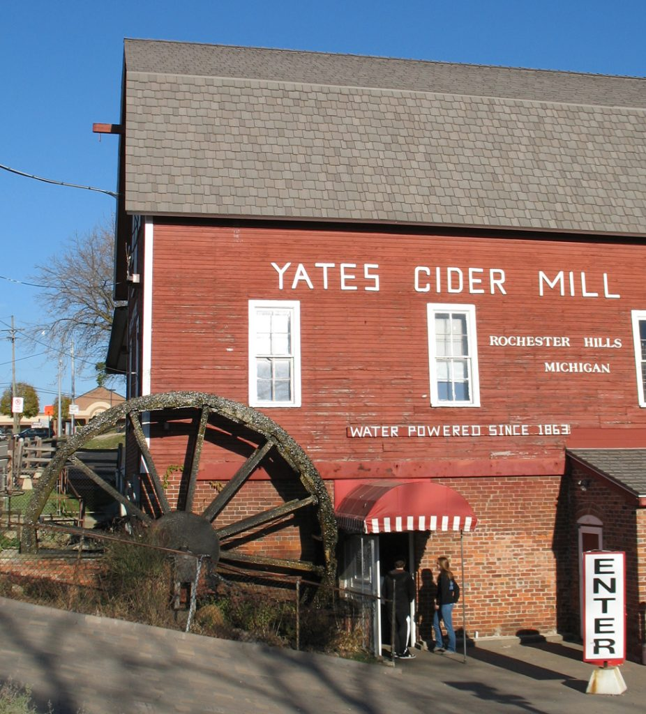 Yates Cider Mill is large red barn-like wood structure with a water-wheel at the corner near the lower entrance door. The ground level is red brick.