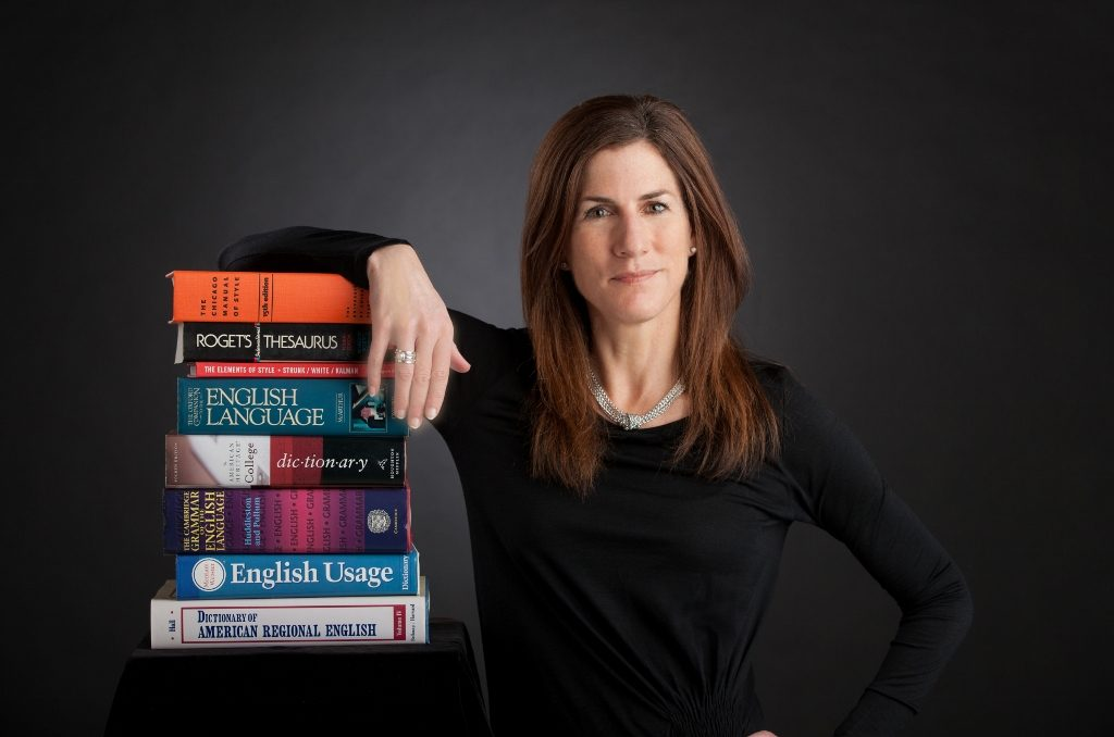 Photo of Anne Curzan standing next to a stack of books on a table, she is resting her arm over them
