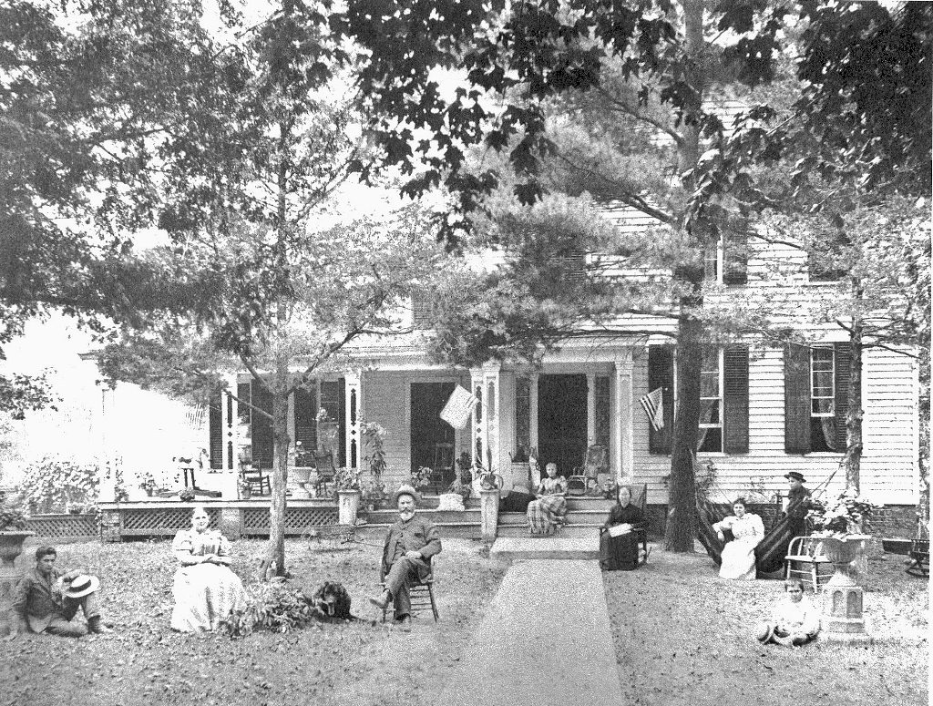 Old photo of a farm house with people sitting in chairs outside