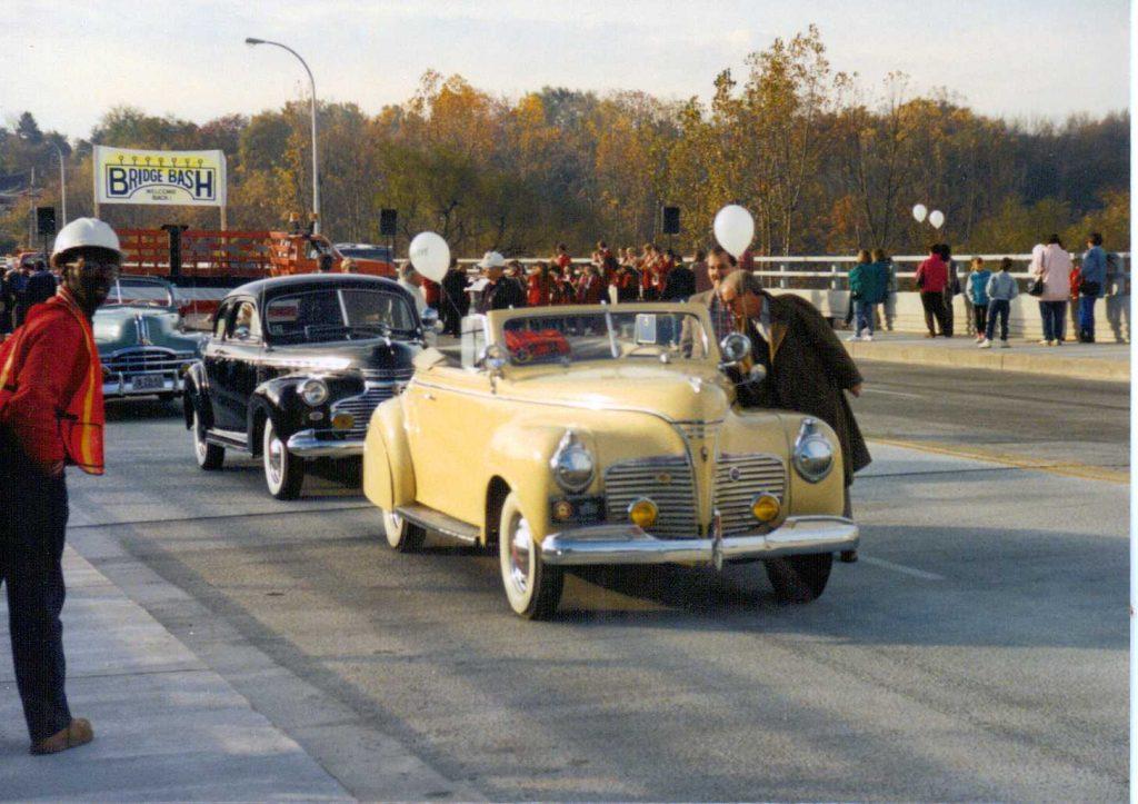 Old cars cross the new bridge
