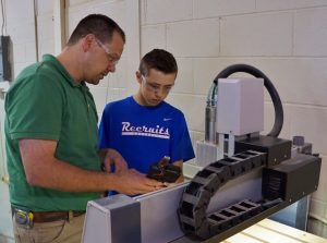 Instuctor and student work on CNC machine