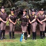 Five officers pose for a photo with a horse and a trophy