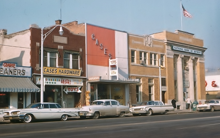 Case's Hardward on Main Steet stands wall to wall with other businesses with several 1960's model cars parked along the street