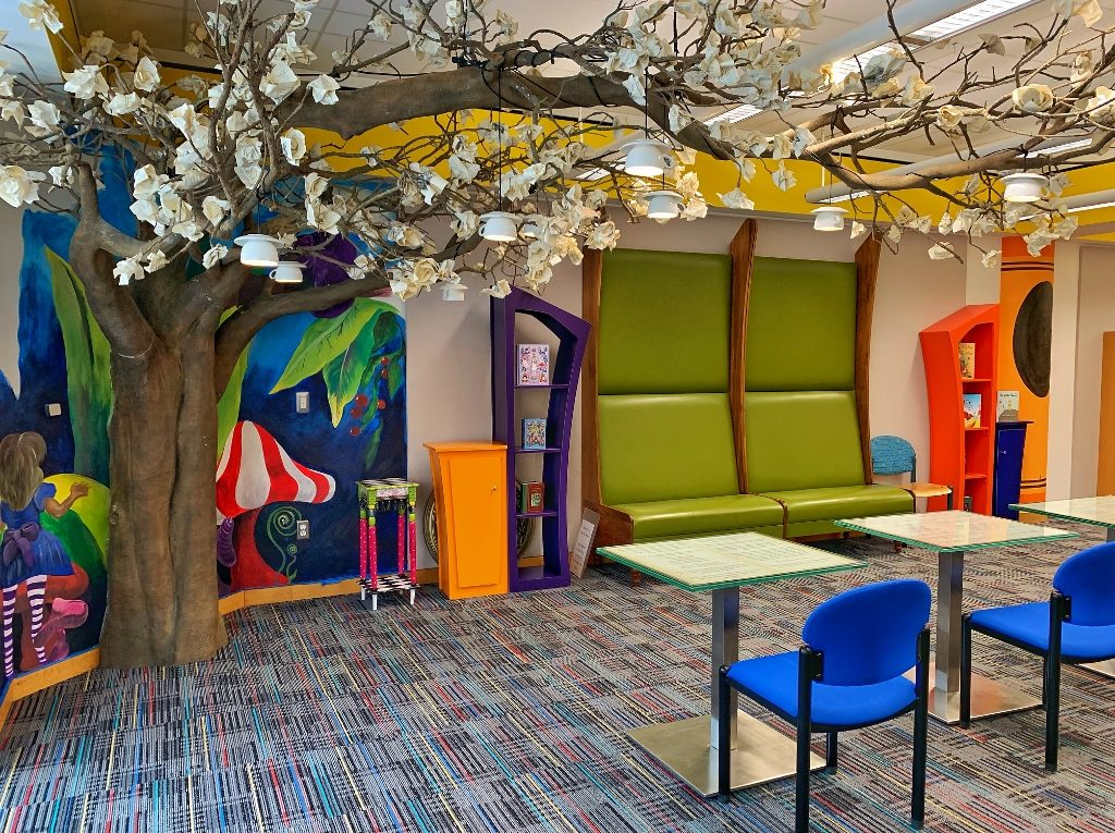 Artificial tree in the toddler & infant area with chairs and tables and mirrors