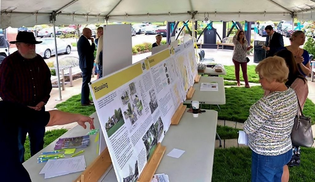 Poeple look at large printed versions of the master plan under a tent at an open house by the city
