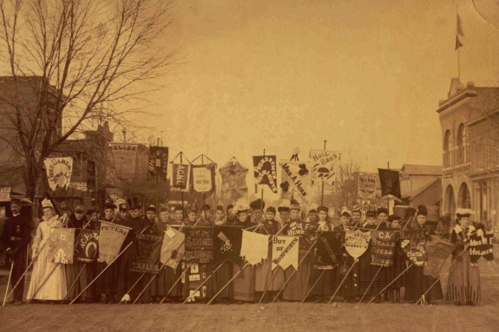 Old photo of a line of people, mostly women, stand across Main Street in Rochester holding signs