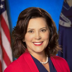Headshot of Governor Gretchen Whitmer with U.S. and Michigan flags behind her.