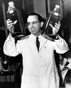 A man in a lab coat holds two gallon-size glass bottles